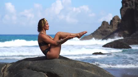 kiegyensúlyozó : A young girl in a bikini balancing sitting on a stone and doing exercises for the abdominal muscles alternately lifting her legs. Training on the background of the ocean on the black sand beach Stock mozgókép