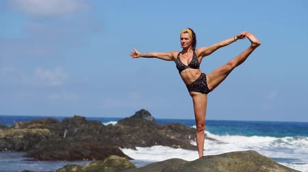 muscular build : Young girl in bikini balancing stands on one leg doing yoga standing on a rock on the ocean beach with black sand. Meditation through relaxation. Gymnastics in the Canary Islands