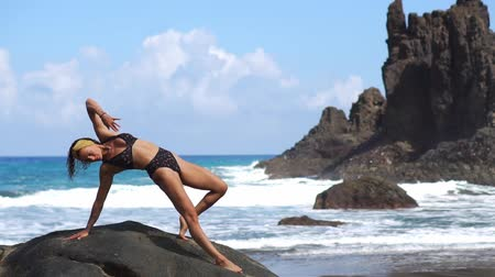 мышечной построить : Woman doing fitness on the beach with volcanic black sand in a swimsuit sitting on a rock around the mountains of lava. The concept of healthy lifestyle and recreation on the Islands Стоковые видеозаписи