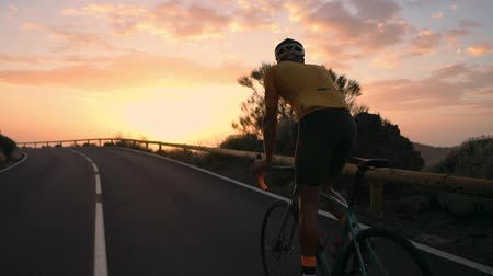 ciclista : A young sports man riding a bike on a mountain serpentine in a yellow t-shirt helmet and sports equipment rear view . Slow motion steadicam