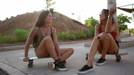 pouze ženy : Two girls in skate Park sit on boards and talk smiling and laughing at jokes in the sunset light. Longboard conversation friends Dostupné videozáznamy