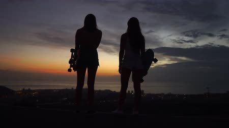 latino americana : Two girls standing on the edge of the road with skateboards in their hands watching the sunset