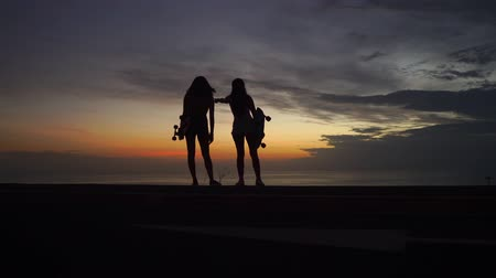 latinamerican : Two girls standing on the edge of the road with skateboards in their hands watching the sunset