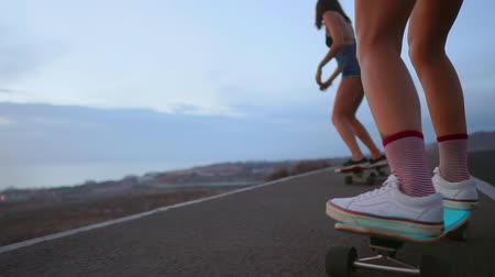 athletes foot : Close - up of a skateboard and two girls who are riding on boards from a mountain on a background of rocks and sky. Slow motion steadicam