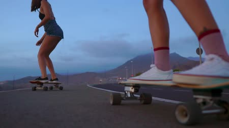 sky only : Close - up of a skateboard and two girls who are riding on boards from a mountain on a background of rocks and sky. Slow motion steadicam