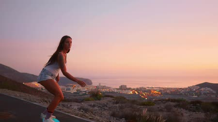 latino americana : Beautiful girl rides a skateboard on the road against the sunset sky Vídeos