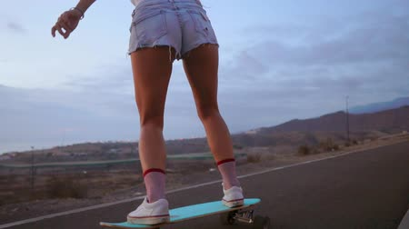 sky only : Female skateboarders on sunset sky background in slow motion steadicam shot. Ride the mountain on the Board Stock Footage