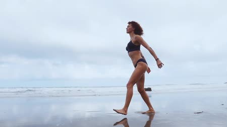 plage : A slender woman near the ocean walking on the water sports to performing lunges on each leg. Exercises for thigh muscles in slow motion Stock Footage