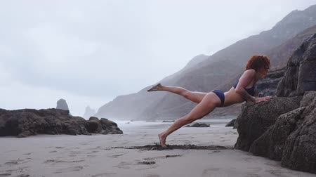 plage : Girl athlete performs pressing from the rock during training on a beautiful beach. Stock Footage