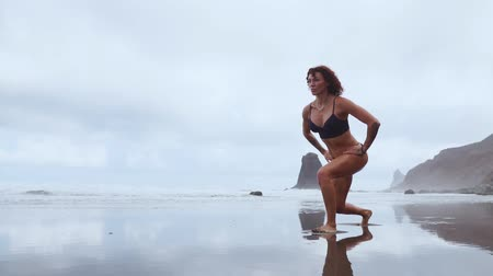 quads : Along the ocean, a woman goes in for sports performing lunges in turn on each leg against the background of rocks and water Stock Footage