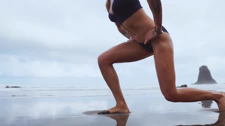 braçadeira : Sport girl on a beach doing lunges exercises. Concept of of a healthy lifestyle. Stock Footage