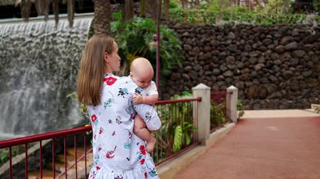 wozek dzieciecy : Mom hugs the baby and walks along the waterfall while traveling to the Canary Islands. Family vacation. Steadicam