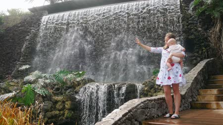 wozek dzieciecy : The baby sitting at his mothers hands laughing and smiling looking at the waterfall during a family trip.