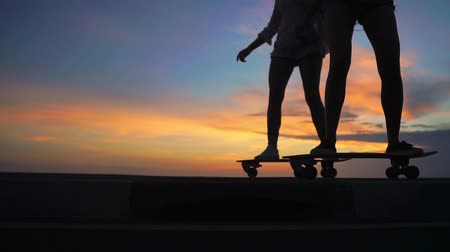 sky only : Close-up of the legs of two girls girlfriend in shorts and sneakers ride skateboards on the slope against the beautiful sky of the rising sun. Slow motion 120 fps