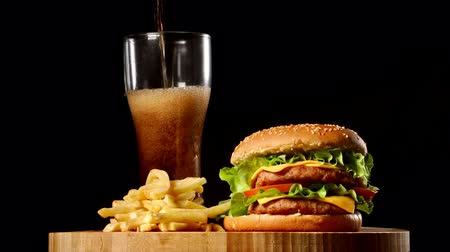 hranolky : Berger and French fries lie on a wooden Board on a black background, close-up poured soda in a glass