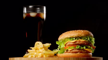 bacon burger : burger with french fries and a glass with ice cola on a black rustic background