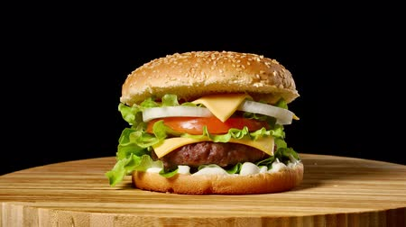 обед : Cheeseburger with bacon on a dark background. Close-up. Macro shooting.