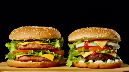 sezam : Close-up of two appetizing burgers with sesame buns rotating on black background, of fast food seamless looping shot . Wideo