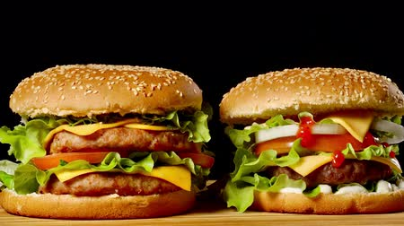 nakrycie stołu : Close-up of two appetizing burgers with sesame buns rotating on black background, of fast food seamless looping shot . Wideo