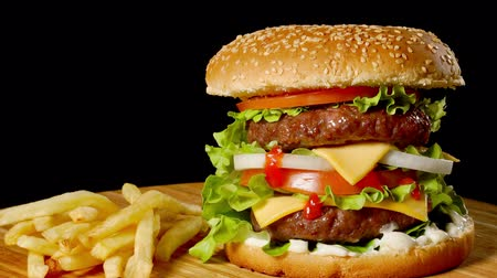 hranolky : Craft beef burger and french fries on wooden table isolated on black background.