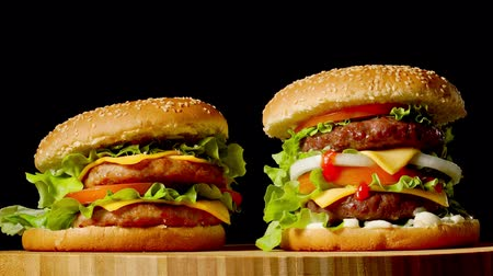 bacon burger : Two craft beef burgers on wooden table isolated on dark grayscale background. Stock Footage
