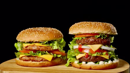 nedvdús : Close-up of two appetizing burgers with sesame buns rotating on black background, of fast food seamless looping shot . Stock mozgókép
