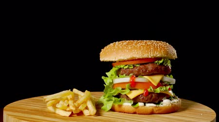 sezam : Craft beef burger and french fries, sauce isolated on black background. fast food