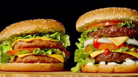 bun : The concept of American fast food. Juicy American burger with two beef cutlets, with sauce and ogretsami on a black background. Copy space