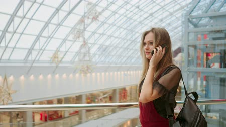 milan fashion : Sale, consumerism: Young woman with smartphones and shopping bags standing and talking near shopping centre Stock Footage