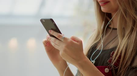 tárcsázás : Happy teenage girl holding bags with purchases, smiling while looking at phone in shopping center. Received good news, reading message, texting. Horizontal photo banner for website header design
