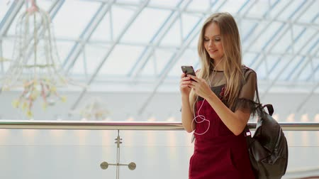 cabeçalho : Happy teenage girl holding bags with purchases, smiling while looking at phone in shopping center. Received good news, reading message, texting. Horizontal photo banner for website header design