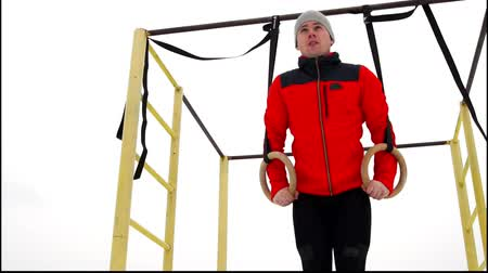 yaşama gücü : A man in a red jacket doing gymnastics Stationary Rings in the open air in the winter