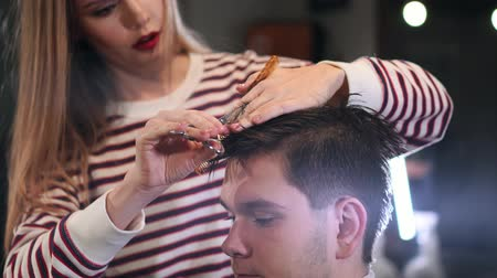 hand on chin : Close-up, master hairdresser does hairstyle and style with scissors and comb. Concept Barbershop.