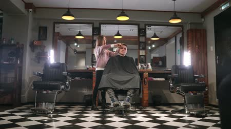 grzebień : Interior shot of working process in modern barbershop. Side view portrait of attractive young man getting trendy haircut. Male hairdresser serving client, making haircut using metal scissors and comb.