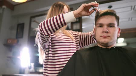 fryzjerstwo : Interior shot of working process in modern barbershop. Side view portrait of attractive young man getting trendy haircut. Male hairdresser serving client, making haircut using metal scissors and comb.