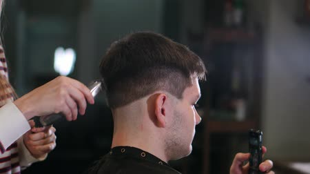 shaver : Close-up view on males hairstyling in a barber shop with professional trimmer. Mans haircutting at hair salon with electric clipper. Grooming the hair.