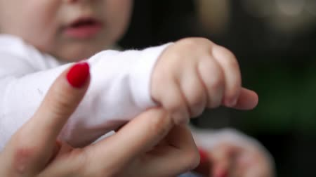 mateřský : Caring mother with baby, Concept of love and family. hands of mother and baby closeup, Hand in hand. Mother care. Playing with baby at home. Slow Motion