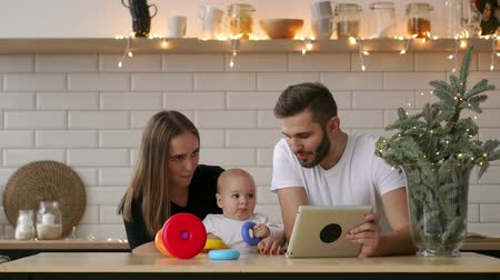 чтение : family of mother, father and baby sitting at home with a tablet PC Стоковые видеозаписи