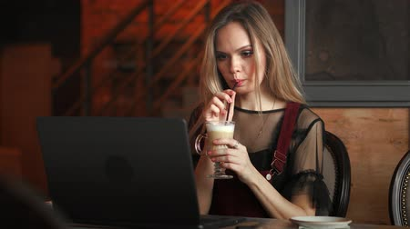 handig : Focused attentive woman in headphones sits at desk with laptop, looks at screen, makes notes, learns foreign language in internet, online study course, self-education on web, consults client by video Stockvideo