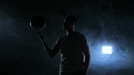 porażka : Basketball player performing different tricks and spinning ball in dark gym with smoke. Slow motion Wideo