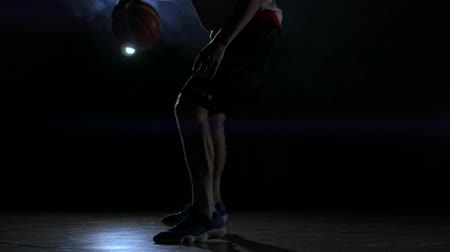 stanovena : Male urban basketball player dribbles ball in crouched position in an inner-city basketball court lit by single street light