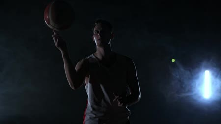 életerő : A man in sports form rotates a basketball on his finger performing a trick looking at the camera on the basketball court around the smoke in slow motion.