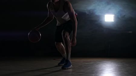 busto : one young adult man, basketball player dribble ball, dark indoors basketball court. Smoke slow motion Vídeos