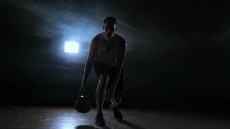 busto : one young adult man, basketball player dribble ball, dark indoors basketball court. Slow motion