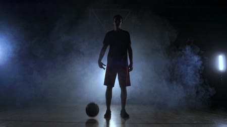 терпение : Basketball player in sportswear red shorts and a blue t-shirt goes on a dark basketball court in the backlighting coming out of the smoke knocks a basketball ball on the floor looking at the camera in slow motion