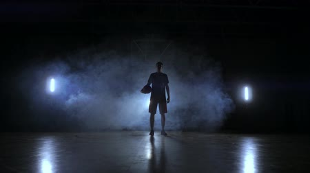 top sürme : The silhouette of a basketball player on a dark background with smoke on the basketball court throws a basket ball and look at the camera in slow motion