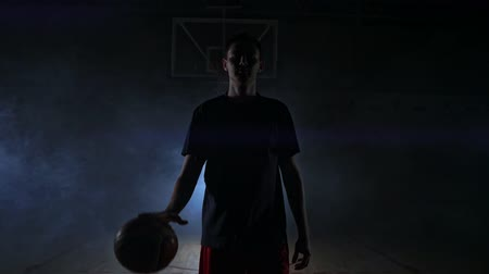 podsvícení : Basketball player in sportswear red shorts and a blue t-shirt goes on a dark basketball court in the backlighting coming out of the smoke knocks a basketball ball on the floor looking at the camera in slow motion