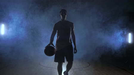 basketbal : Male basketball player moving in the smoke at the camera knocking the ball about the parquet ground in slow motion Steadicam shot