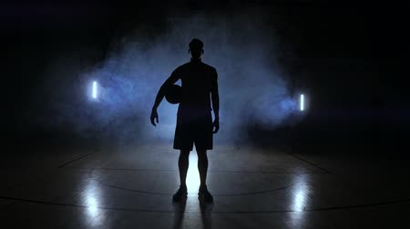 sahte : Basketball player knocks the ball in the light of the lamps shining behind stands in the Duma and knocks the ball on the floor in the basketball hall in slow motion