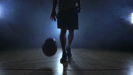 crossover : Male basketball player moving in the smoke at the camera knocking the ball about the parquet ground in slow motion Steadicam shot